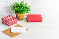 Red dotted gift box, empty card, kraft envelope, red book and a green flower in a rustic ceramic pot. White wooden background, cop