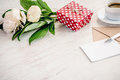 Red dotted gift box, kraft envelope and empty greeting card, coffee cup and peony flowers bouquet over white wood background. Copy Royalty Free Stock Photo