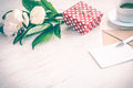 Red dotted gift box, kraft envelope and empty greeting card, coffee cup and peony flowers bouquet over white wood background. Copy