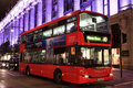 Red double decker bus at night Stock Image
