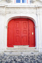 Red double door and cobblestone ground at the entryway of a building with stairs on b w Stock Photo