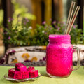Red Dragon fruit juice in a glass with two glass straws, cut dragon fruit on a glass plate. Flowers on a background. Royalty Free Stock Photo