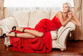 Red dress beautiful blonde woman in long posing on sofa Royalty Free Stock Image