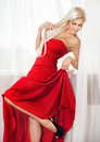 Red dress beautiful smiling blonde woman in long pose against window Stock Image