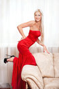 Red dress beautiful smiling blonde woman in long pose against window Stock Photography