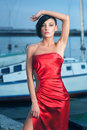 Red dress beautiful young woman in glossy posing on marina Royalty Free Stock Image