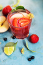 Red drink in glass with slices of apple, strawberry and lime Royalty Free Stock Photo