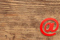Red e-mail symbol on wooden background with copy space Royalty Free Stock Photography