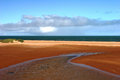 Red earthed estuary and ocean at carnarvon western australia und blue skies id Royalty Free Stock Photography