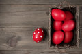 Red easter eggs in basket traditional and dotted on wood background top view point Stock Images