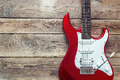 Red electric guitar on grunge wooden planks background. Place fo Royalty Free Stock Photo