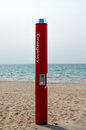 Red emergency phone beach has blue flashing light attached event emergency Royalty Free Stock Photo