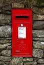 Red english letterbox a traditional mounted in a dry stone wall in the village of buttermere in the lake district national Stock Images
