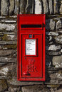 Red english letterbox a traditional mounted in a dry stone wall in the village of rydal in the lake district national park Royalty Free Stock Photo