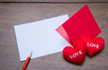 Red envelop with shape heart pillow on text love sheet of paper and wooden background Royalty Free Stock Photo