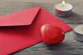 Red envelop with stone heart and candles on wooden background Stock Photography