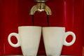 Red espresso machine pours coffee into two cups Royalty Free Stock Photo