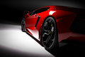 Red fast sports car in spotlight, black background. Shiny, new, luxurious. Royalty Free Stock Photo