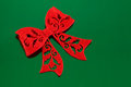 Red felt bow on green with decorative cutouts a background Stock Photography