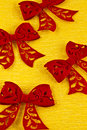 Red felt bows on a yellow crêpe paper Stock Photos