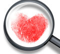 Red fingerprint in heart shape through magnifying glass Royalty Free Stock Images