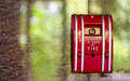 Red fire alarm on the marble wall with the park outside reflection Royalty Free Stock Photo