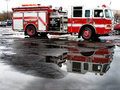 Red fire engine parked in street with reflection puddle Stock Photos
