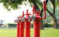 Red fire hydrant fire main pipe for fire extinguishing typical hydrants in a row on the lawn pipes prevention pipes fighting and Royalty Free Stock Photos