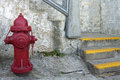 Red fire hydrant by the staircase with grunge textured wall background Stock Photos