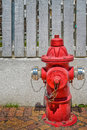 Red fire hydrant in the street with a wooden fence background Royalty Free Stock Photos