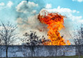 Red fire with smog under clouds Royalty Free Stock Photo