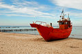 Red fishing boat on the seashore with blue sky in background Stock Photography