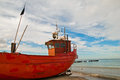 Red fishing boat on the seashore with blue sky in background Royalty Free Stock Images