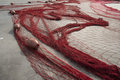 Red fishing net on the ground in a sicilian harbour Stock Photo