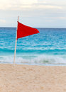 Red flag on the beach close up in a sunny day Stock Images