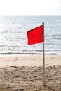 Red flag on the beach season of storms Royalty Free Stock Image