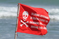 Red flag with no swimming sign on the sand beach Royalty Free Stock Images