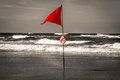 Red flag in ocean in selective color B&W during Surf competition, Lacanau, France Royalty Free Stock Photo