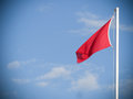 Red flag for rough sea over a lifeguard tower long an Italian be Royalty Free Stock Photo