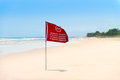 Red flag on the sand beach Royalty Free Stock Photo