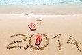 Red flip flops on the beach and digits sand concept of summer vacations and new year Royalty Free Stock Photos