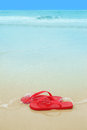 Red flip flops beach sand concept summer vacations Stock Photo