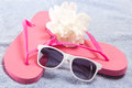 Red flip flops sunglasses and flower over towel white Stock Image