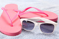 Red flip flops and sunglasses over towel white Royalty Free Stock Image