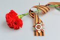 Red flower tied with Saint George ribbon and order of Great Patriotic war Royalty Free Stock Photo