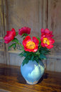 Red flowers in a vase on a wooded table arrangement of Royalty Free Stock Photo