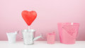 The red foiled chocolate heart stick with small silver watering can and small pink bucket Royalty Free Stock Photo