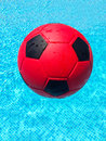 Red football in a swimming pool and black Royalty Free Stock Images