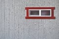 Red framed window on grey wooden wall Royalty Free Stock Photo