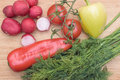 Red fresh radish, tomato, green and red pepper and green dill on wooden kitchen board Royalty Free Stock Photo